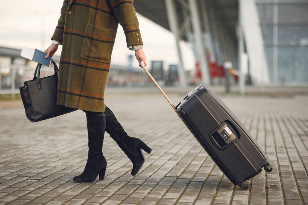 Mujer camina con una maleta en el aeropuerto.
